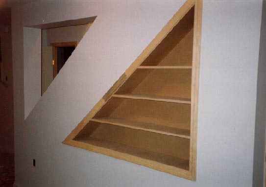 Built-in bookcase under stairs in finished basement